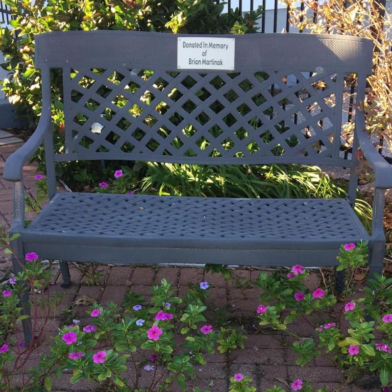 Nice black wrought iron bench by the daylilies